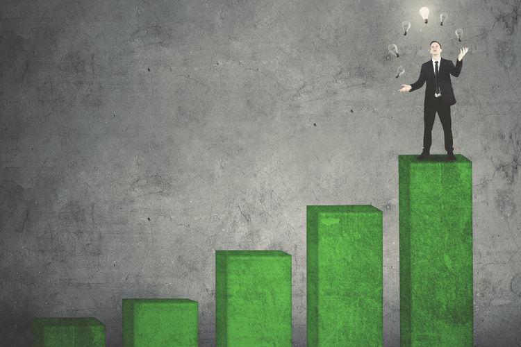 Businessman Juggling Light Bulbs On Green Graph Against Wall