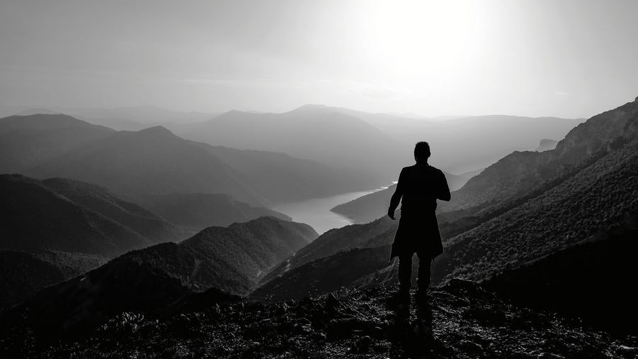 Silhouette man standing on mountain against sky during foggy weather