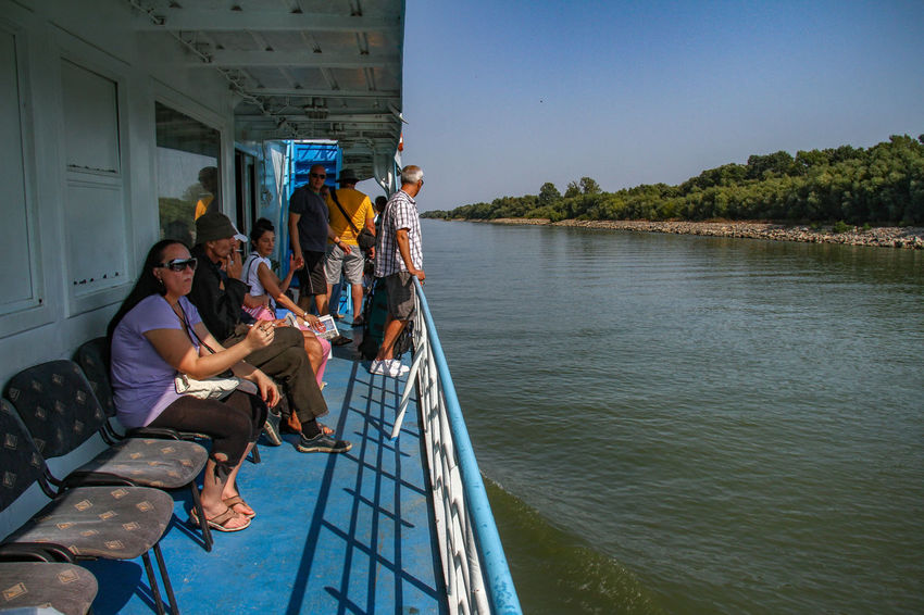 Danube Delta Danube Ferryboat Architecture Built Structure Clear Sky Day Enjoyment Friendship Full Length Leisure Activity Lifestyles Men Nature Nautical Vessel Outdoors People Real People River Sitting Sky Togetherness Water Waterway To Sulina Women