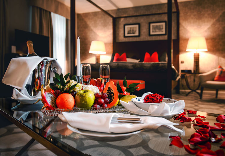 Luxury hotel room is ready for a romantic evening with champagne, fruits and rose petals Bed Bright Colors Champagne Champagne Glasses Lux Romantic Romantic Date Room Rose Petals St. Valentine's Day Bedroom Champagne Flute Exotic Fruits Flowers Fruits Hotel Hotel Room Ice Bucket Illuminated Interior Interior Design Luxury Nobody Red Rose Wealth