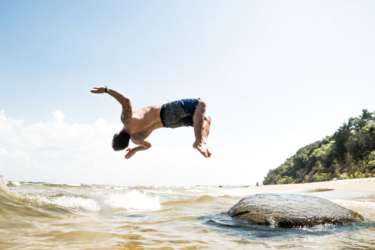 Day Enjoyment Excitement Freedom Full Length Holiday Human Arm Jumping Leisure Activity Lifestyles Men Mid-air Motion Nature Outdoors People Positive Emotion Real People Rock - Object Sea Sky Water Waterfront