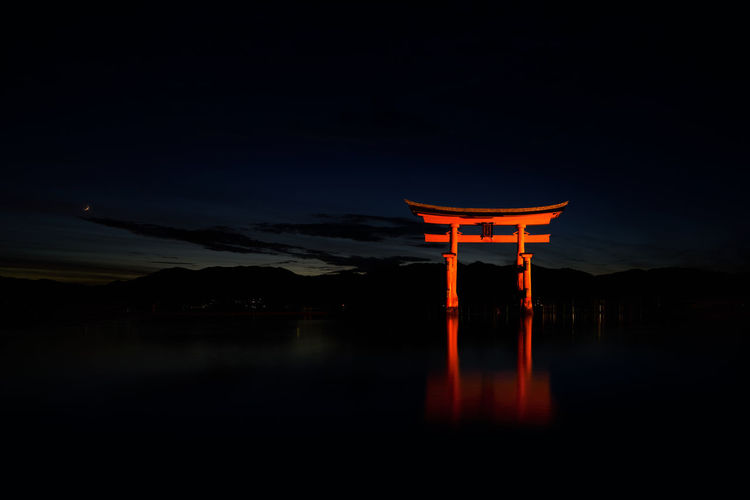 Illuminated temple by lake against sky at night