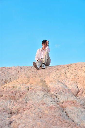 A person sitting on a rock with a bright blue sky