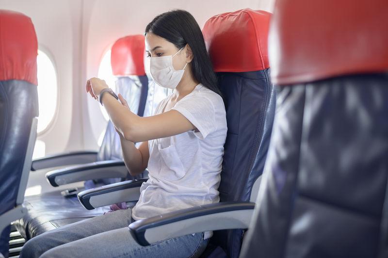 Woman wearing mask sitting in airplane
