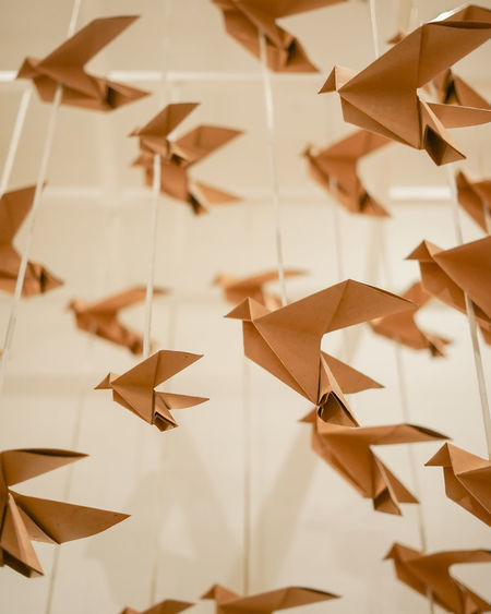 Close-up of paper toy hanging against white wall