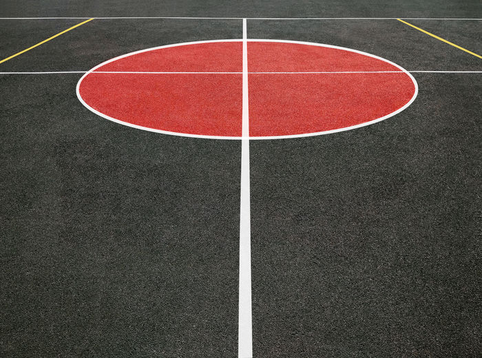 Perspective view of center circle of sports field with white lines. black and red playing ground