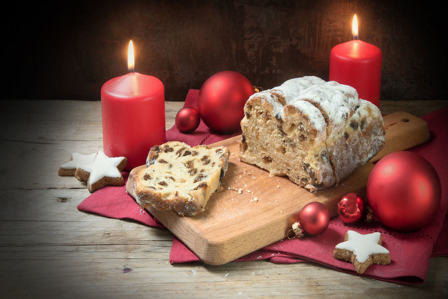 German Christmas cake, called criststollen with raisins and fruit, decoration from star cookies, red candles and balls on rustic wood, dark background Advent Christmas Holiday Baking Burning Cake Candle Celebration Christmas Decoration Christmas Ornament Christstollen Flame Food Food And Drink Illuminated Indoors  No People Red Stars Table Wood - Material