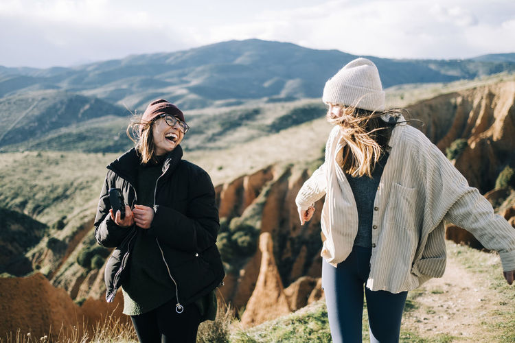 Friends standing on mountain against sky
