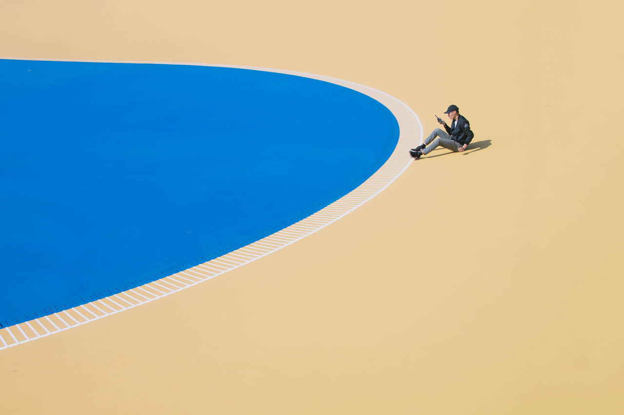 HIGH ANGLE VIEW OF MAN PLAYING IN POOL