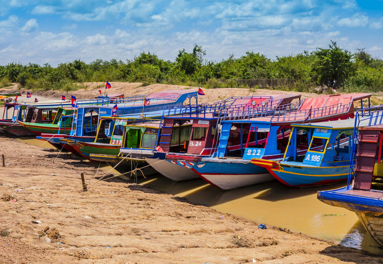 View of boats moored on beach against sky