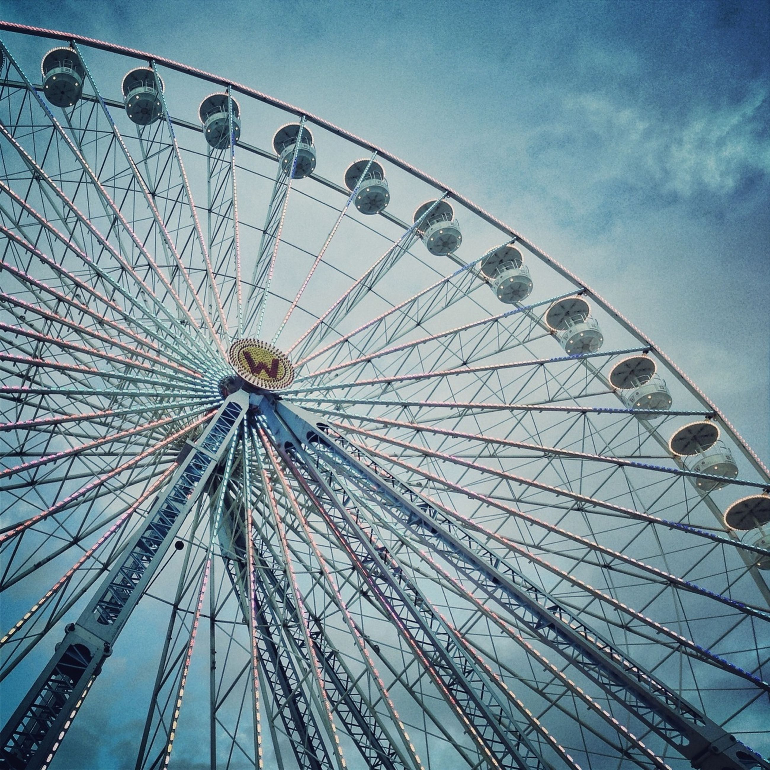 amusement park, ferris wheel, amusement park ride, arts culture and entertainment, low angle view, sky, blue, big wheel, built structure, large, fun, fairground, enjoyment, metal, fairground ride, outdoors, day, leisure activity, rollercoaster, architecture