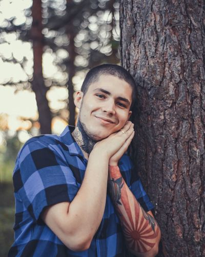 Portrait of smiling young man standing by tree trunk