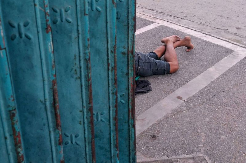 Low section of man lying on street