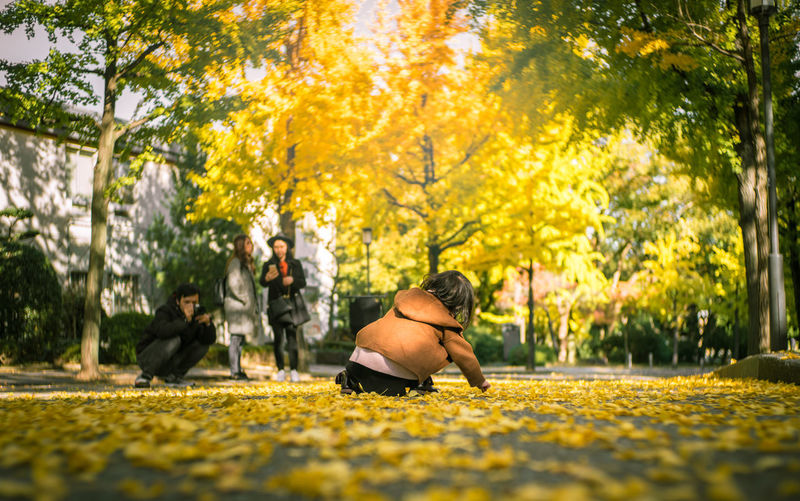 Rear View Of Girl Playing With Fallen Autumn Leaves In Park