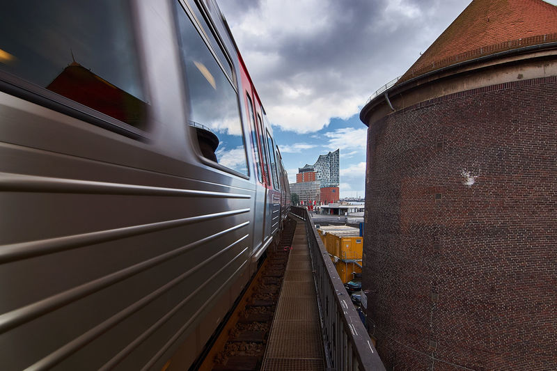 Train on railroad track against cloudy sky in city