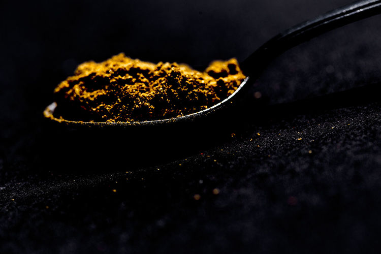 Close-up of turmeric powder in spoon at table