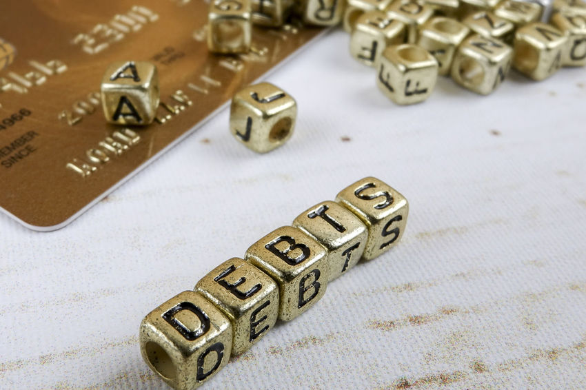 DEBT CONCEPT WITH GOLD DICE ON A WOODEN TABLE Close-up Communication Credit Card Debt Crisis Finance Gold Colored High Angle View Indoors  Jewelry Large Group Of Objects Luxury Metal No People Number Paper Personal Accessory Selective Focus Shiny Silver Colored Still Life Studio Shot Table Text Wealth Western Script