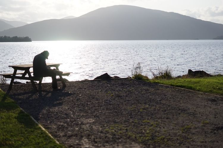 Woman sitting on bench by lake against mountains