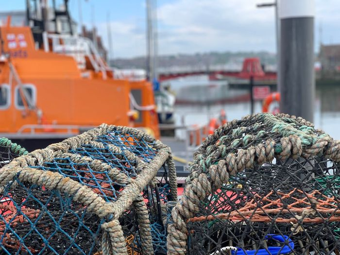 Lifeboat and crab pots EyeEm Selects Day Harbor Transportation No People Fishing Industry Architecture Mode Of Transportation Nature Fishing Focus On Foreground Water Nautical Vessel Built Structure Large Group Of Objects Sky Outdoors Abundance City Building Exterior Stack