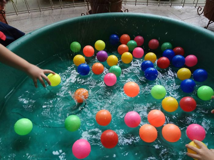 High angle view of children playing with balls floating on water in container