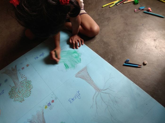 High angle view of girl drawing on paper while sitting on floor