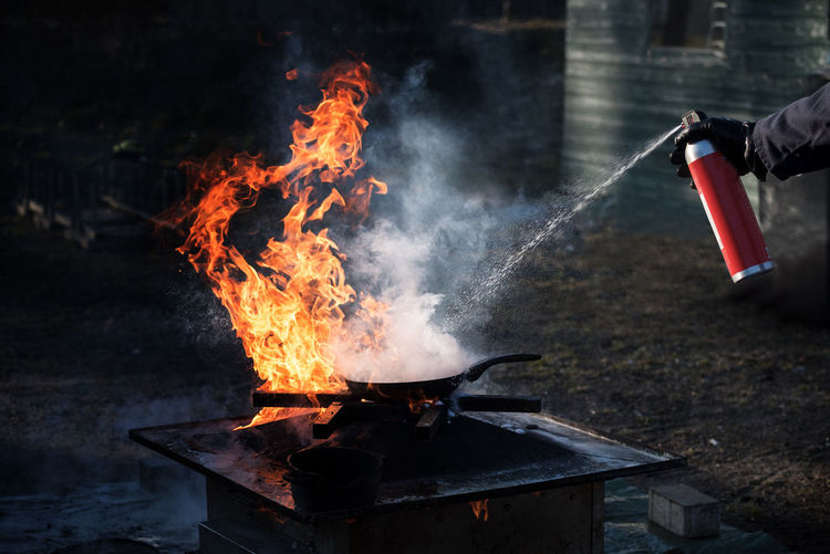 Man extinguishing the fire on an iron pan with foam from a spray can, demonstration during a fire department training, dark background with copy space Dark Flame Smoke Barbecue Burning Can Danger Dangerous Day Demonstration Extinguishing Fighting Fire Fireman Flame Foam Grill Hand Heat Heat - Temperature No People Outdoors Pan Spray Training