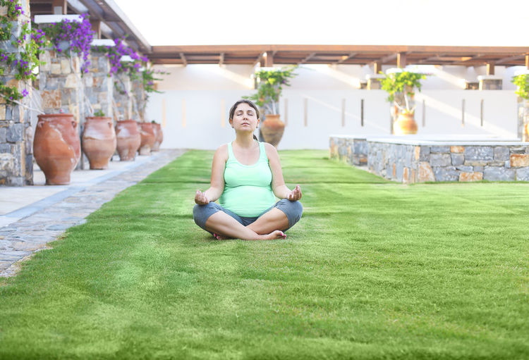 Full length of pregnant woman meditating on grassy land
