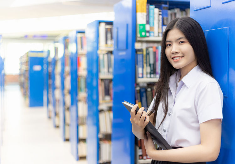 Portrait of young woman holding book while standing in library