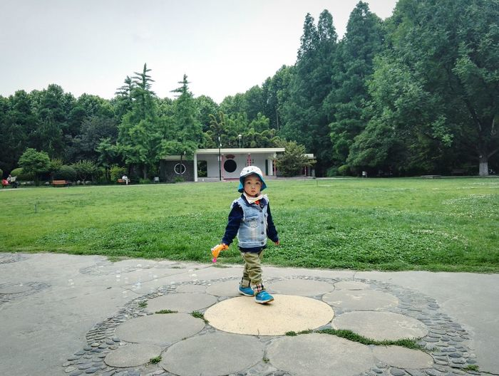 Portrait of smiling boy standing on field against trees