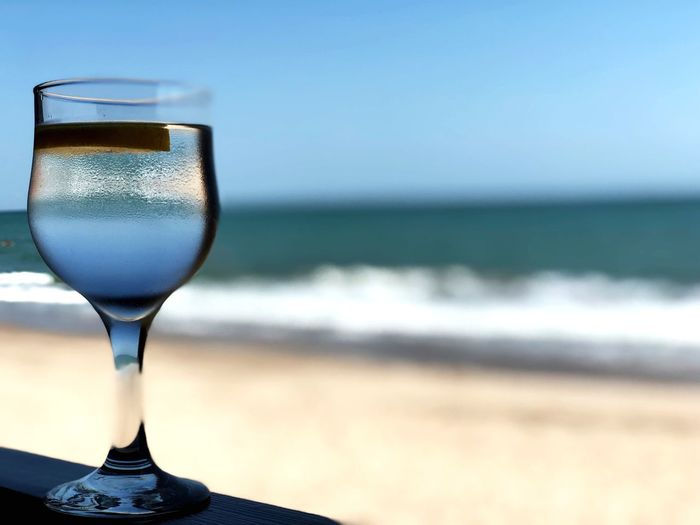 Close-up of beer glass on beach against sky