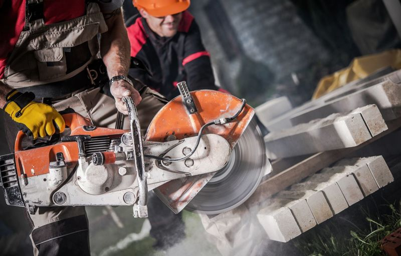Midsection of worker using circular saw at construction site