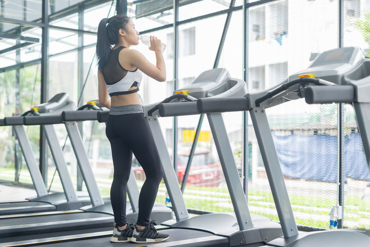Young woman drinking water from bottle on treadmill at gym