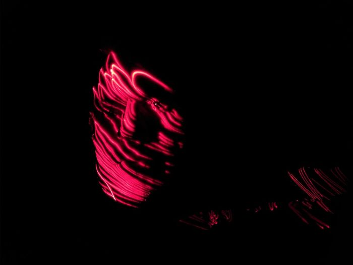 Close-up of illuminated red light against black background