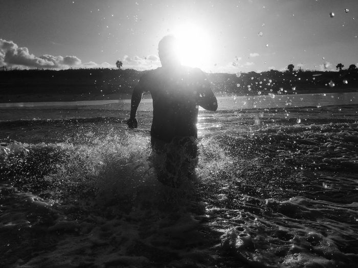 Running Beach Beauty In Nature Front View Land Leisure Activity Lens Flare Lifestyles Men Nature One Person Outdoors Real People Silhouette Sky Splashing Sports Standing Sun Sunlight Three Quarter Length Water