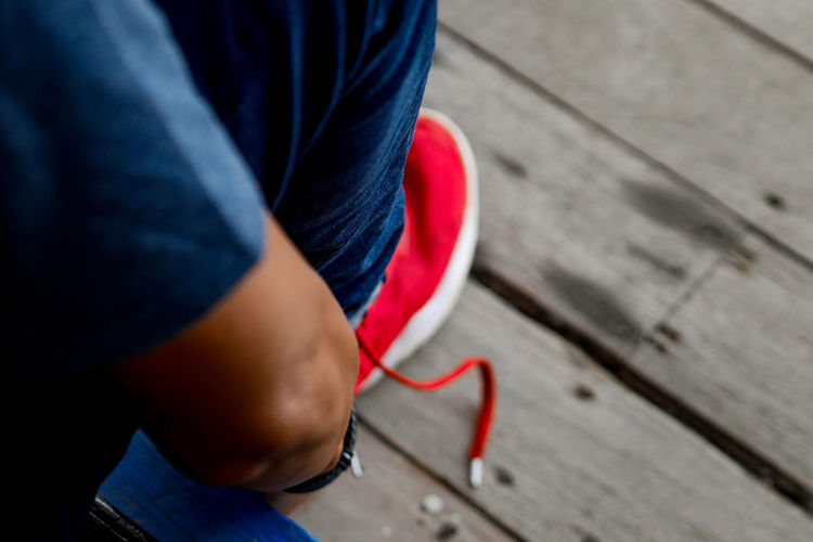Low section of man wearing red shoes