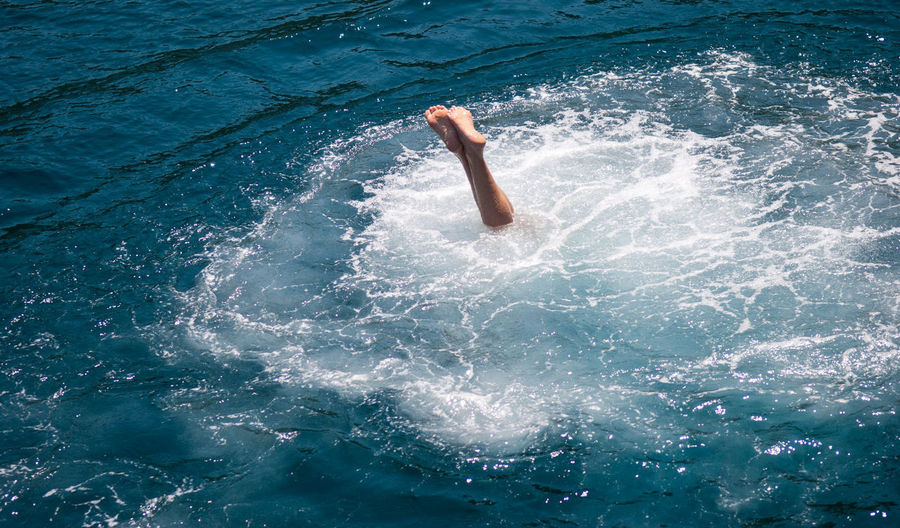 Low section of person diving into water