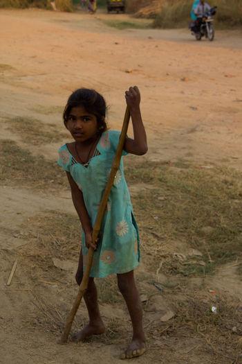 Full length portrait of homeless girl holding stick on field