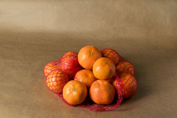 Clementines in nets on brown paper - supermarket packaged food Citrus  ClementinesDay Freshness Snack Supermarket Brown Brown Paper Citrus Fruit Clementine Clementines Fruit Healthy Healthy Food Ingredient Mandarins Monochromatic Monochrome Mood Nets Obst Orange Color Packaging Peel Pile Still Life