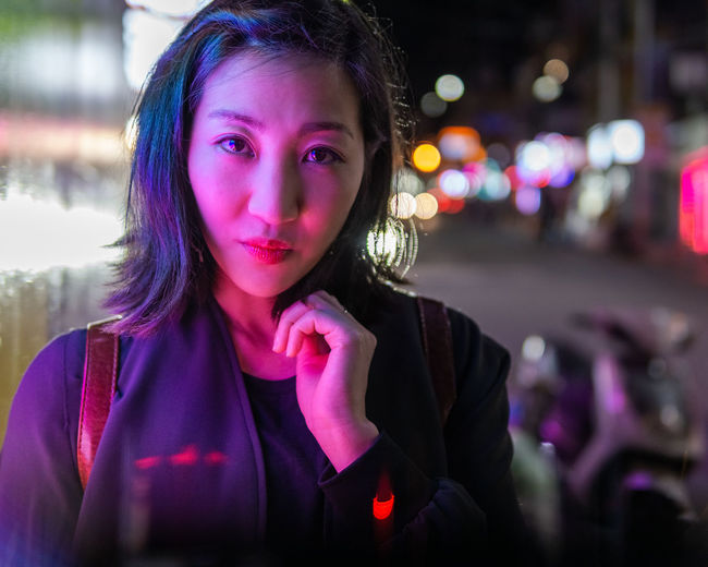 Close-up portrait of beautiful woman in city at night