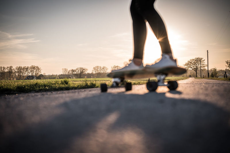 Low section of person skateboarding on road