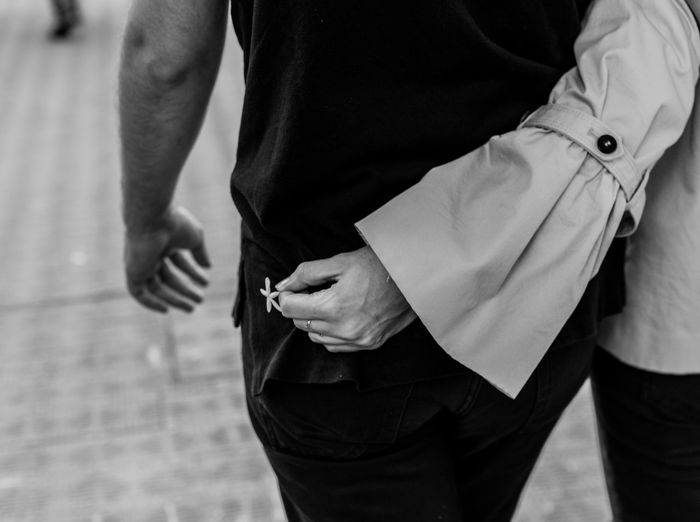 Midsection of woman holding flower while walking with boyfriend on footpath
