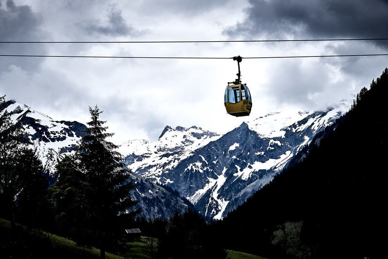 Overhead cable cars over snowcapped mountains against sky