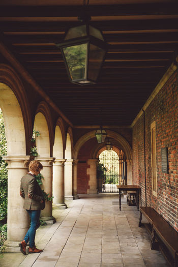 Full length of woman standing by architectural columns in corridor