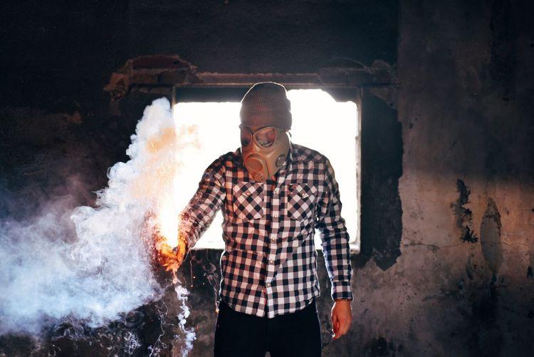Man wearing gas mask holding smoke bomb in abandoned house