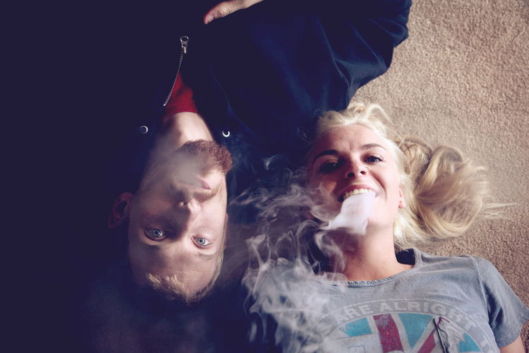 High Angle Portrait Of Couple Smoking While Lying On Carpet At Home