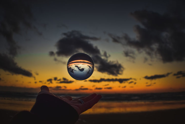 Silhouette person holding lensball against sky during sunset