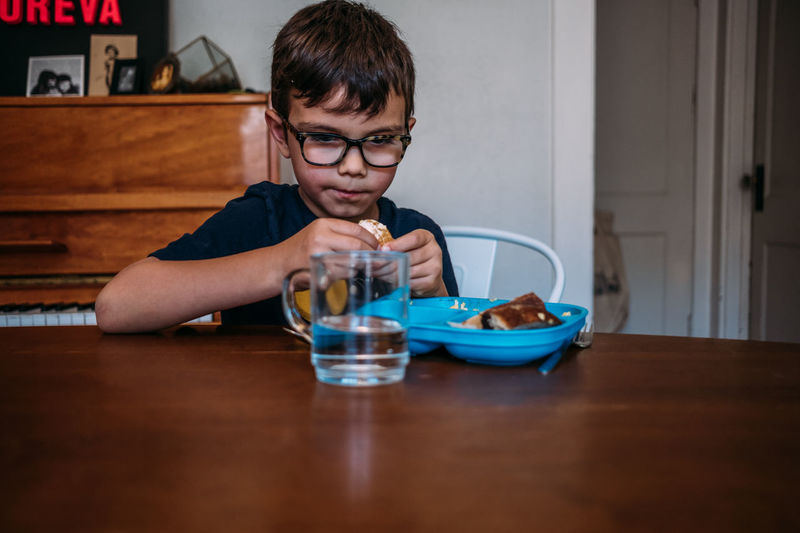 Portrait of boy with drink sitting on table