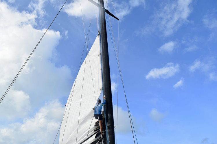 Low angle view of man standing on sailboat against blue sky