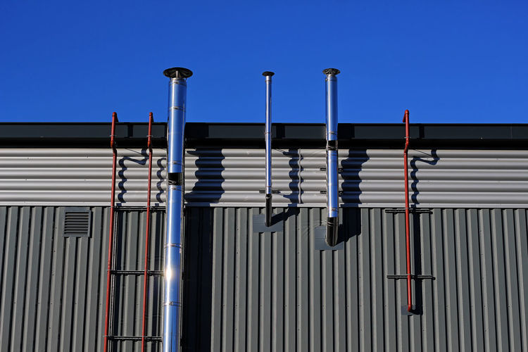 A Family of Pipes Architecture Blue Building Building Exterior Built Structure Clear Sky Corrugated Corrugated Iron Day In A Row Iron Lighting Equipment Low Angle View Metal No People Outdoors Pattern Sky Striped Sunlight