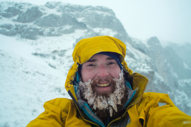 Portrait Of Young Man With Frozen Beard Standing Against Mountain During Winter